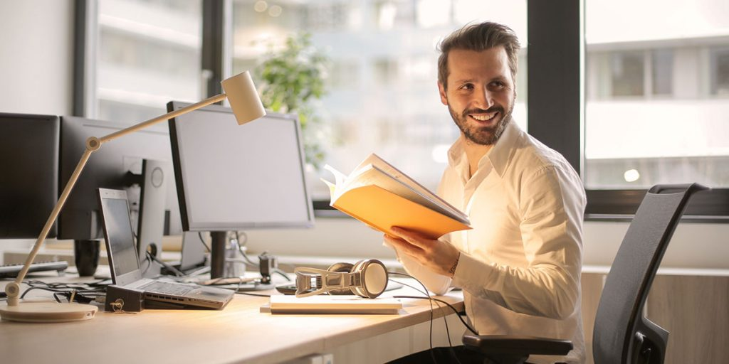 smiling man sitting at desk with book in hand
