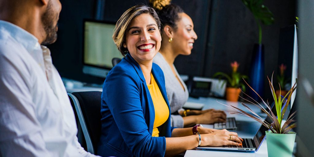 woman on laptop smiling at coworker