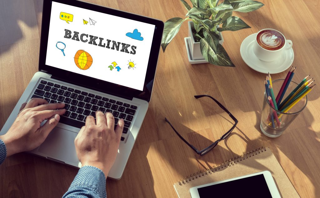 laptop with a screen that says backlinks on a desk with coffee mug, pencils, and glasses